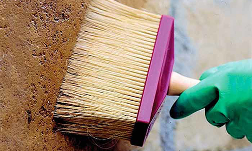 Кисть пропитывает бетонную стену